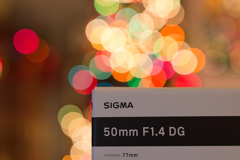 sigma 50mm art lens box with Christmas tree bokeh