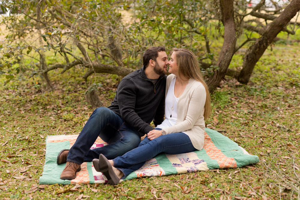 cute couple seated on vintage quilt under live oak tree (Ocean Springs, Mississippi)