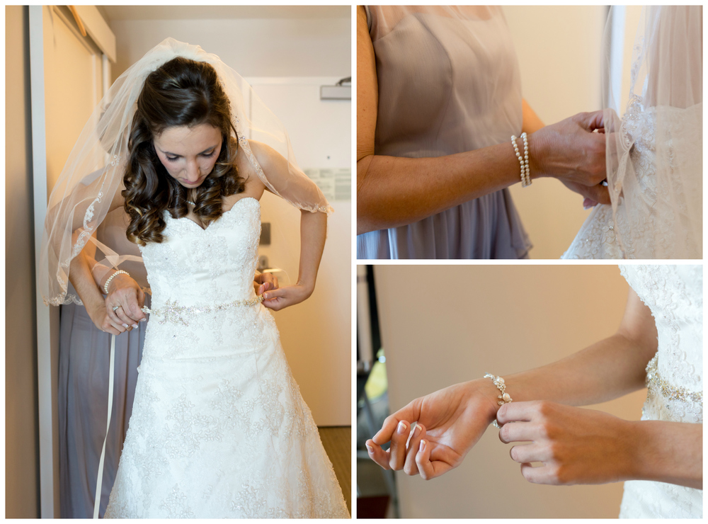 bride getting dressed with belt, bracelet, mom zipping dress