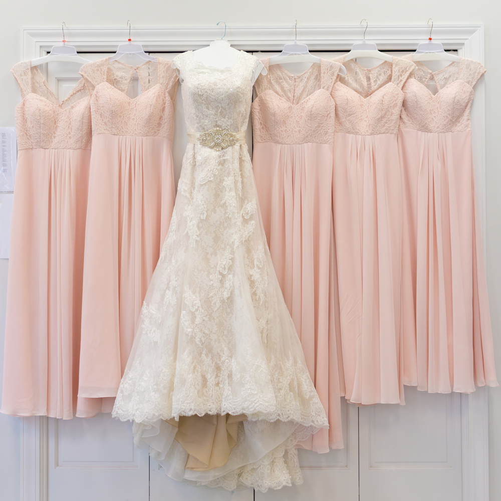 bridal gown and pink lace bridesmaids dresses hanging up