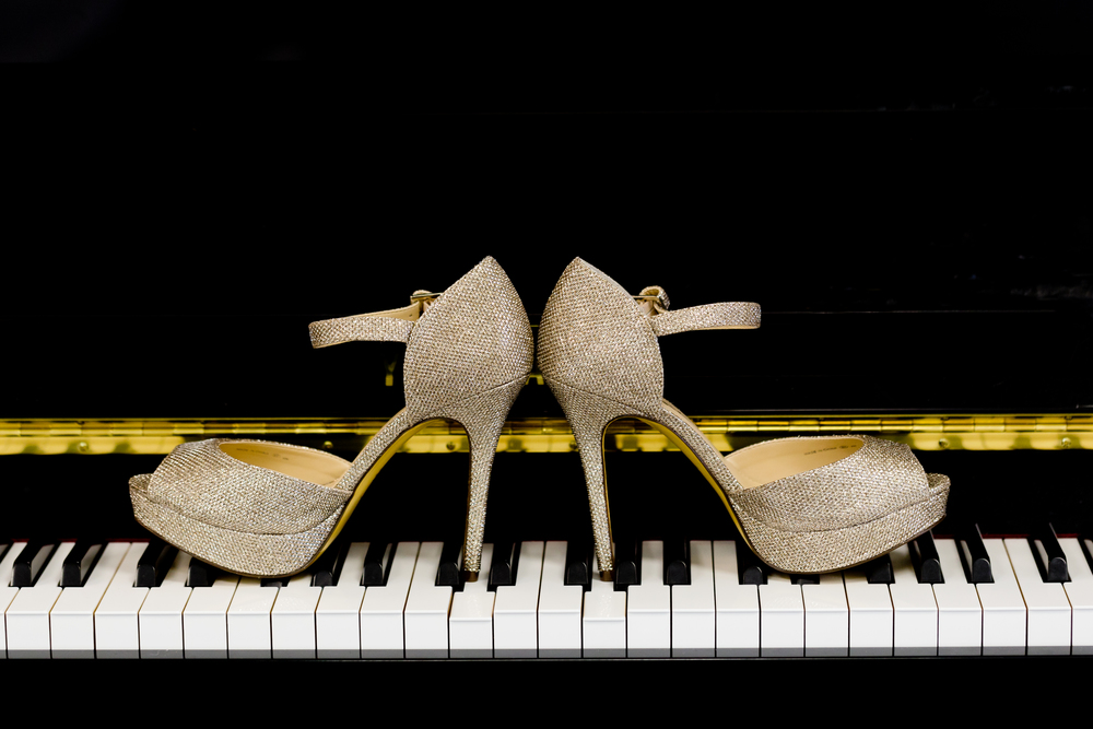 bride's high heel platform gold sparkly shoes on piano