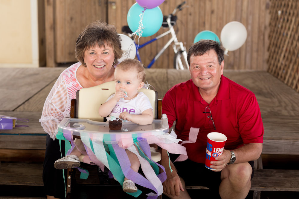grandparents with granddaughter on first birthday