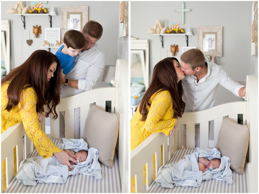 newborn baby in crib with family looking on (lifestyle photo in nursery)