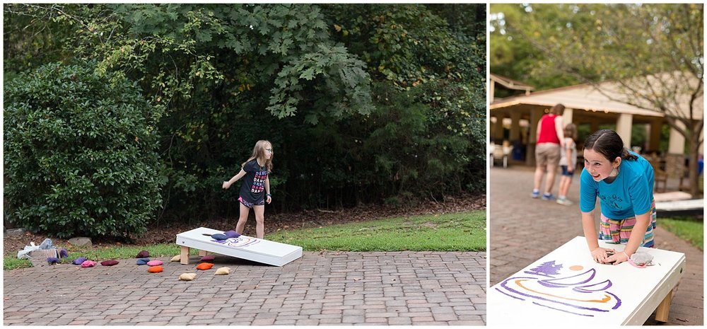 little girls playing corn hole at casual rehearsal dinner at camp