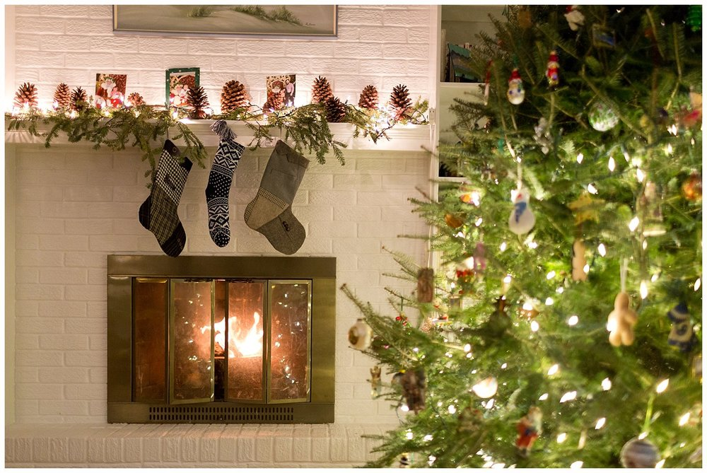 stockings on mantel with fire in fireplace and Christmas tree