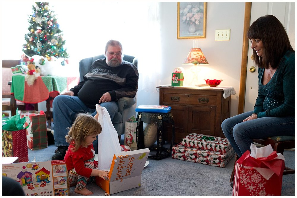little girl opening Christmas present with great aunt and uncle