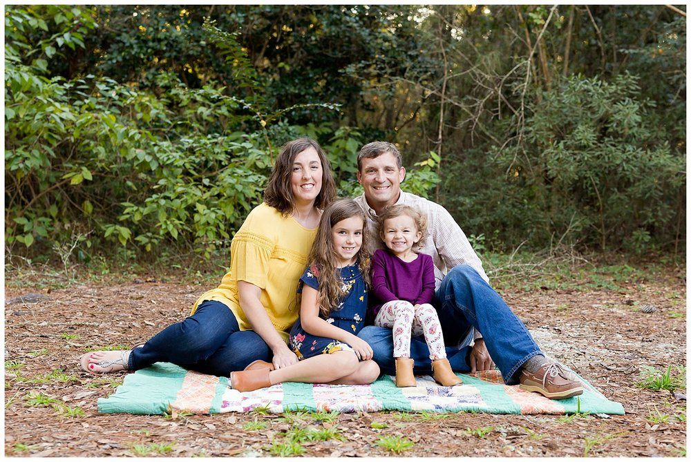 family portraits in Ocean Springs, Mississippi - family of four seated on a vintage quilt in the woods