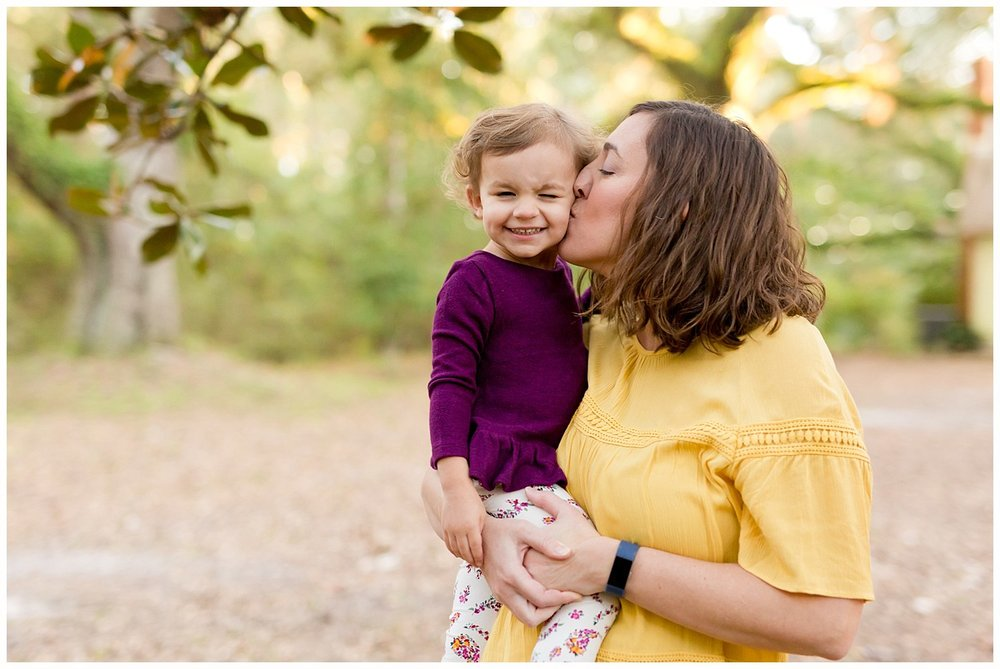 mom kissing 2-year-old daughter on the cheek