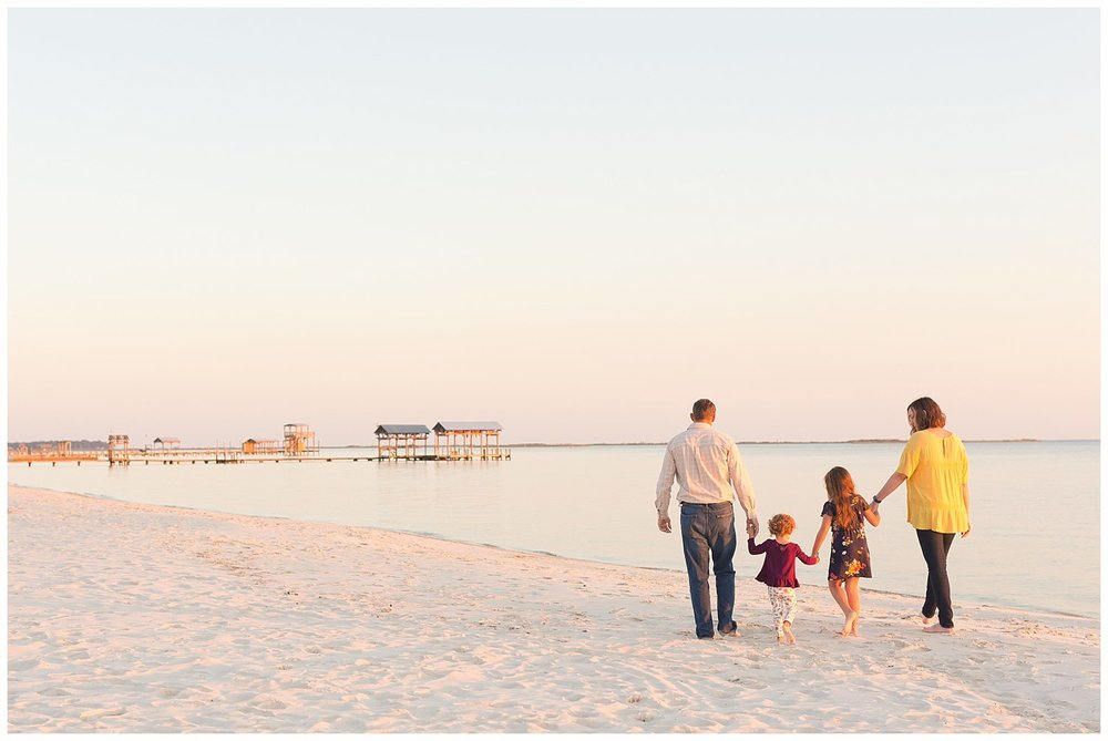 family of four walking on Ocean Springs East Beach