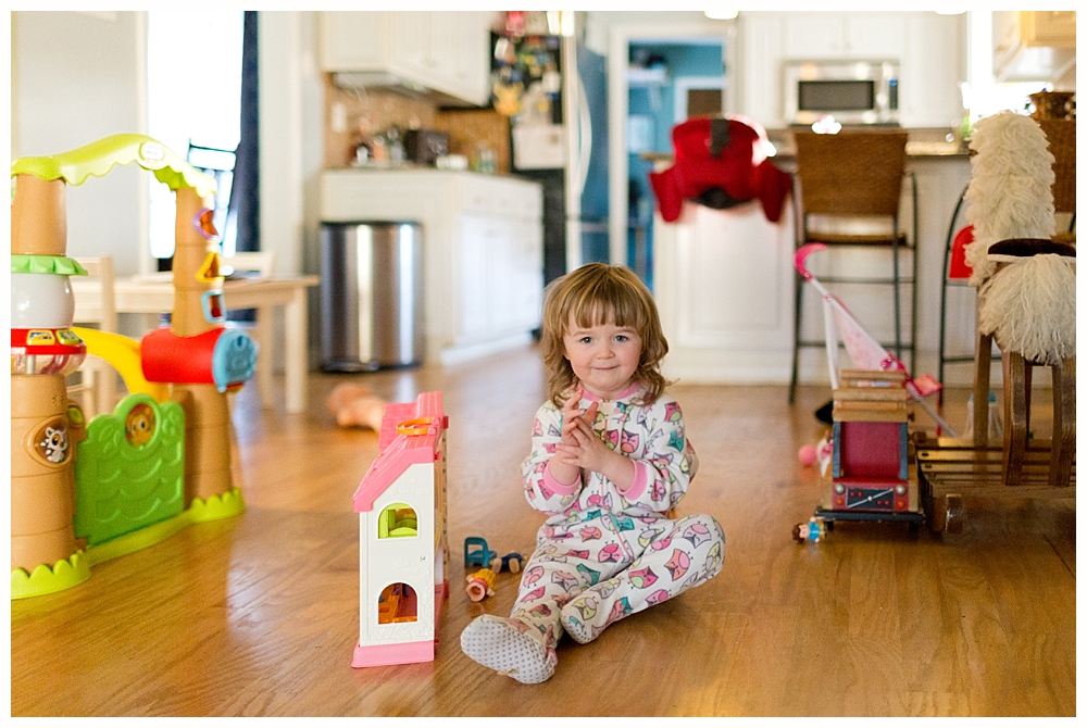 2-year-old girl playing with dollhouse