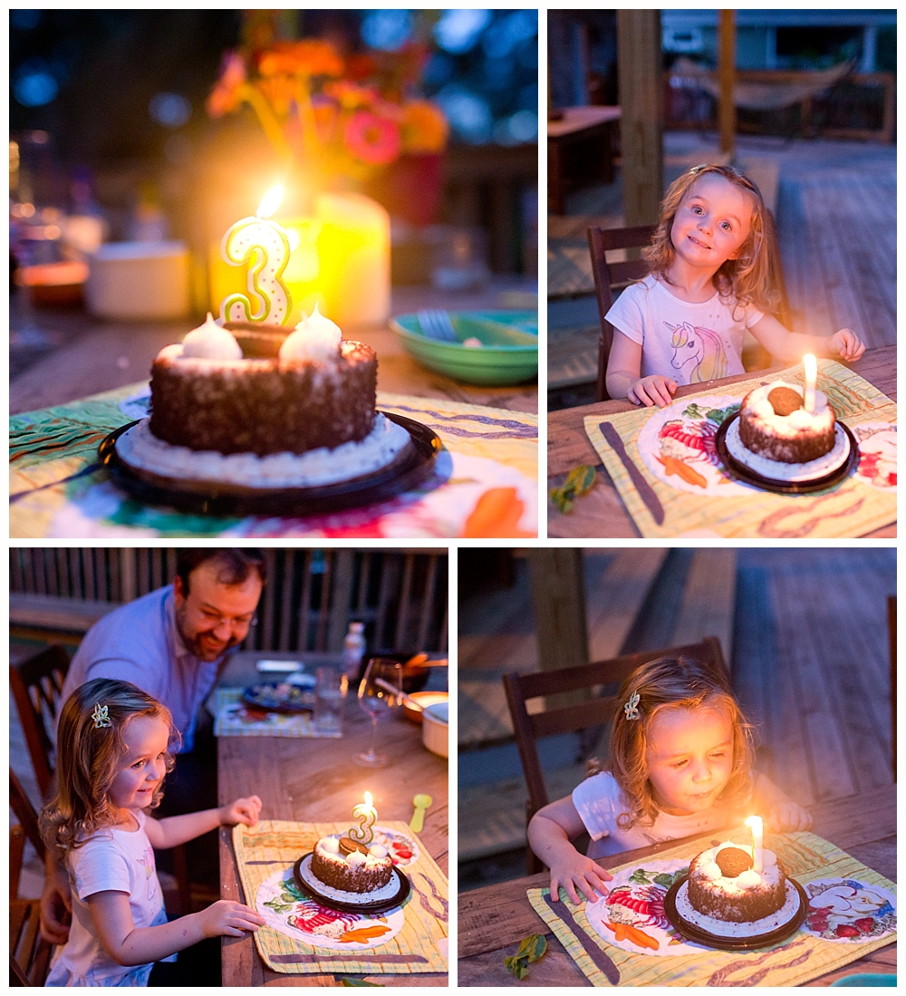 little girl blowing out candles on third birthday cake