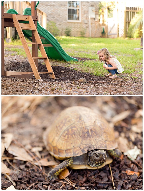 little girl and turtle in backyard