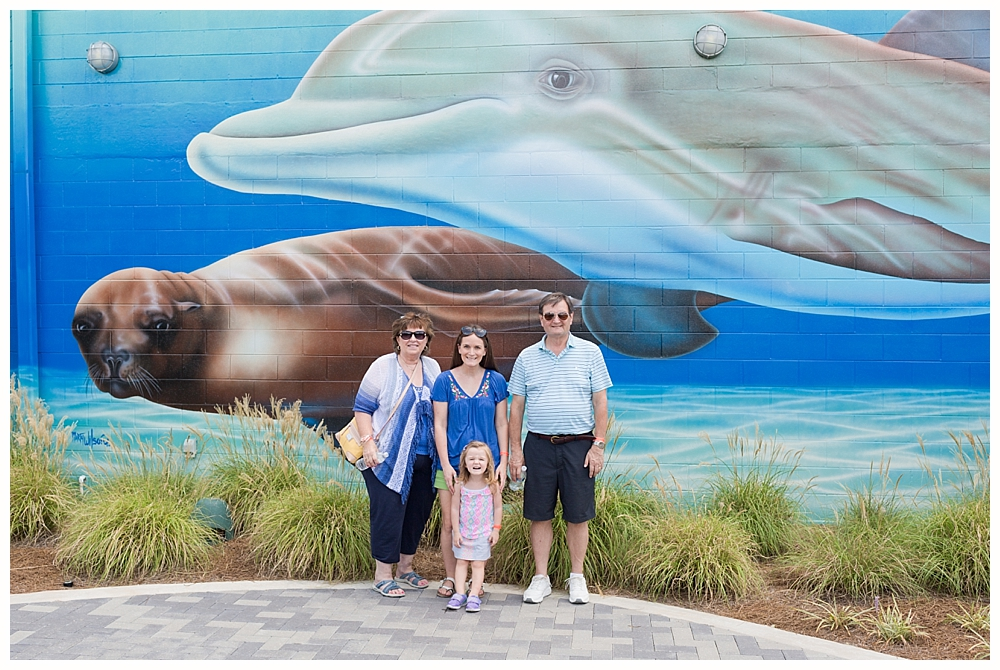 family photo with mural at Ocean Adventures Marine Park in Gulfport, Mississippi