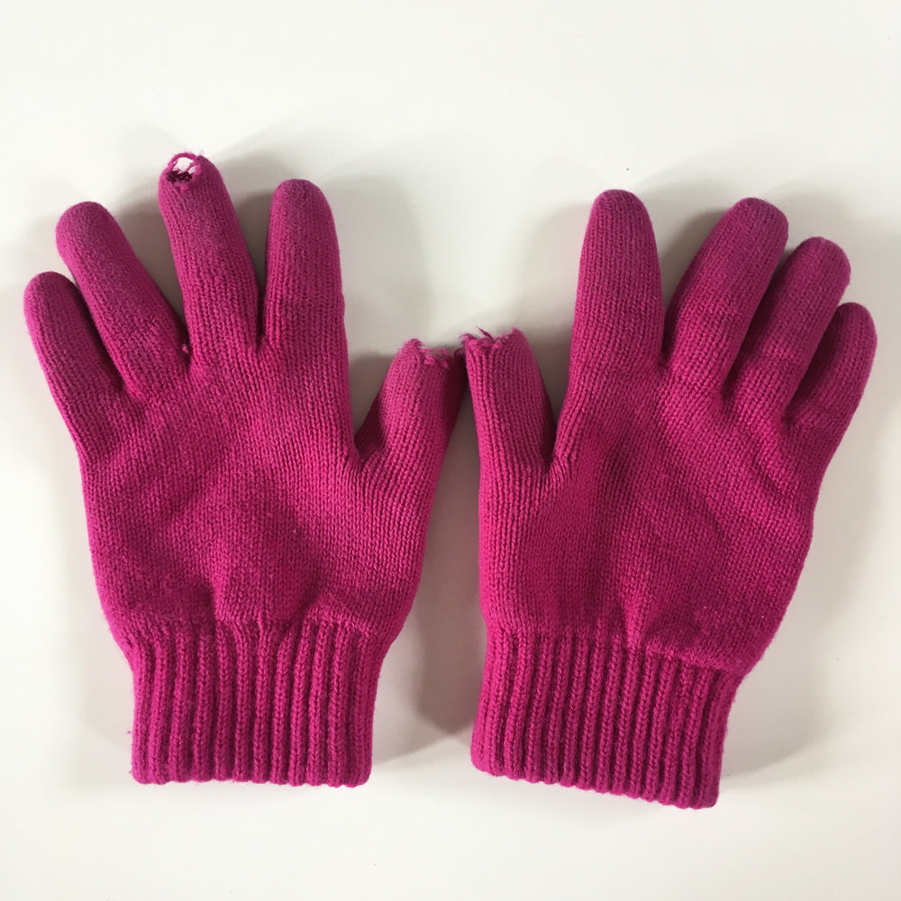 A pair of cashmere gloves with holes in both thumbs and a finger.