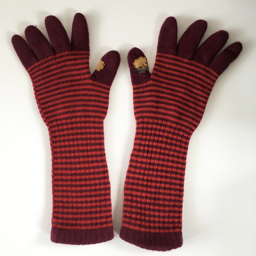 The finished gloves, one with a darned hole, and the other with swiss darning to reinforce worn area.