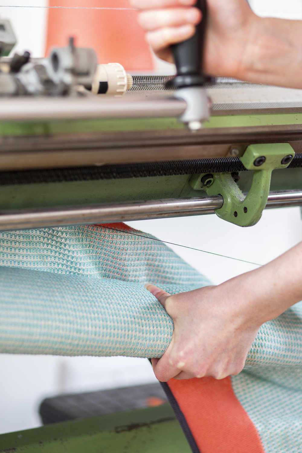 Taking the scarf off the knitting machine.