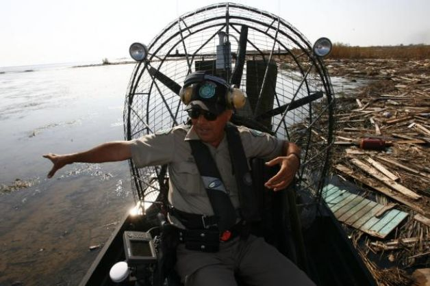 Hector Gonzalez uses his airboat to skim across  debris field in Chambers County after Hurricane Ike.jpg