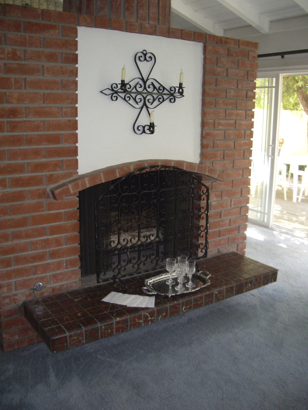 Before: Original brick fireplace, blue carpeting was throughout the house.