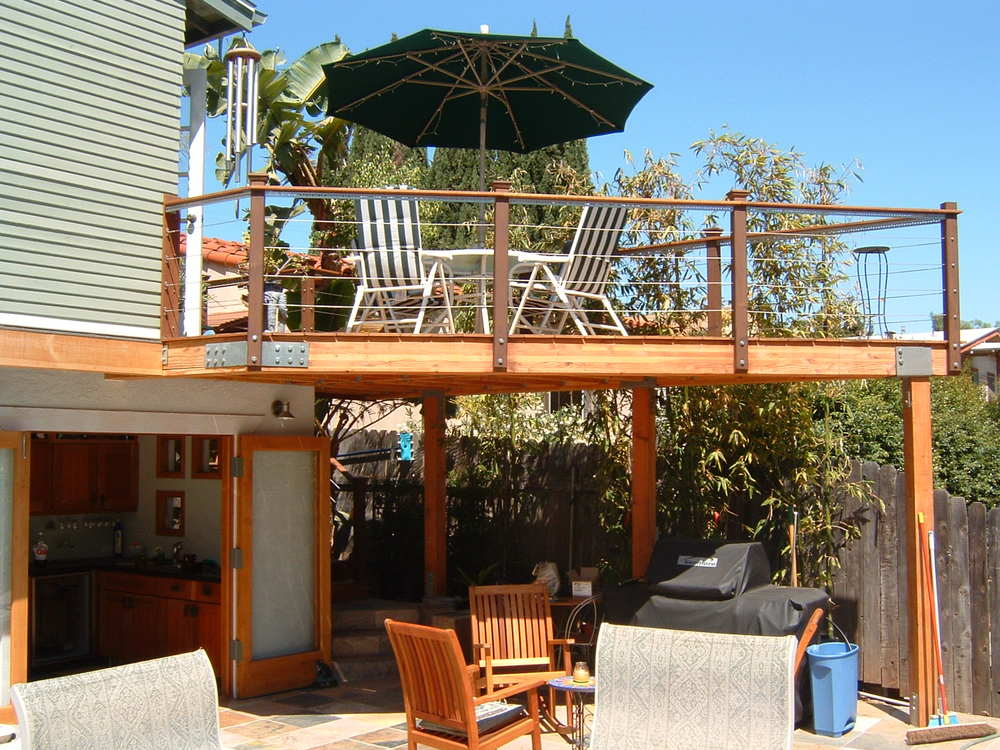 A beautiful angular deck with cable railings and an exterior stairway provide visual and physical access to the kitchen.