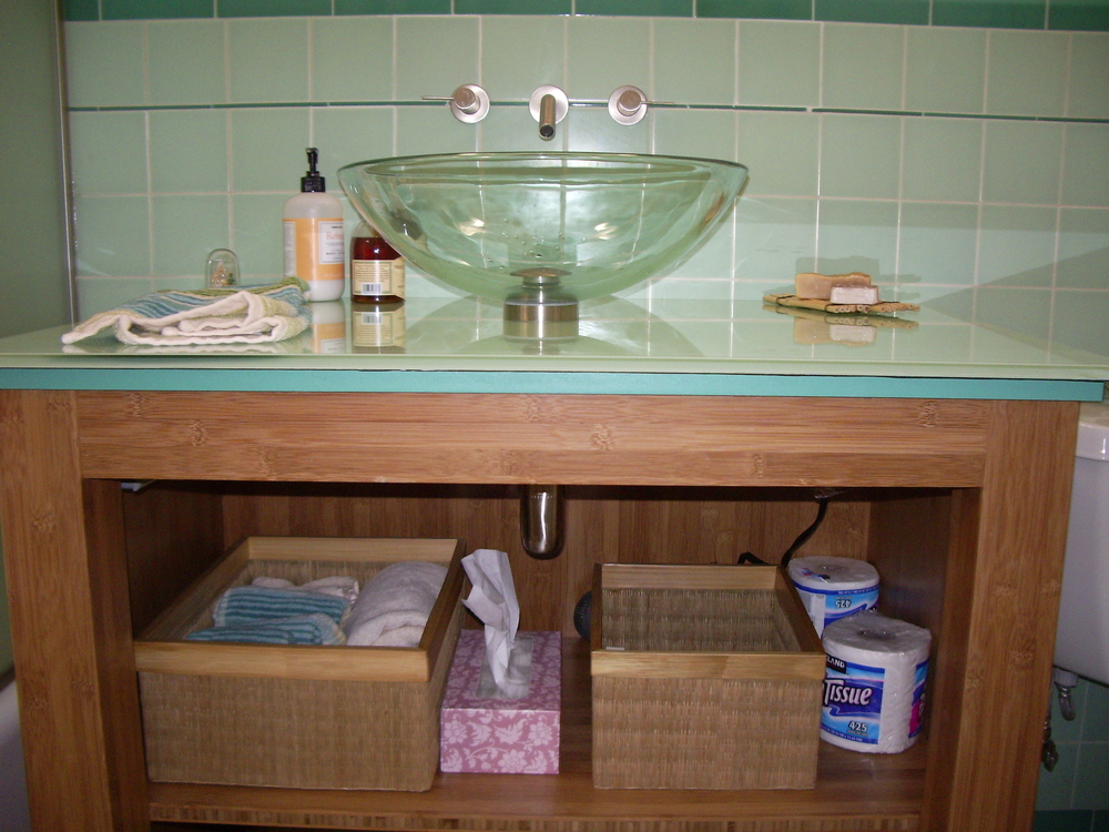 After: Bamboo plywood vanity with custom back-painted glass countertop.