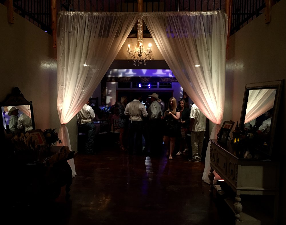 Elegant entrance created with sheer draping, crystal chandeliers, and uplighting.