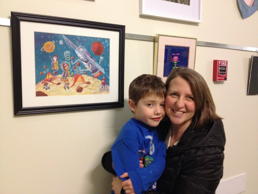 "Mitzie with her son Alec in front of her painting ""Spaghetti Planet"""