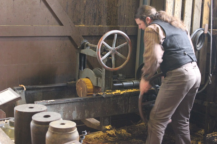 A man building the spokes for a wheel at a 'wheelery'.