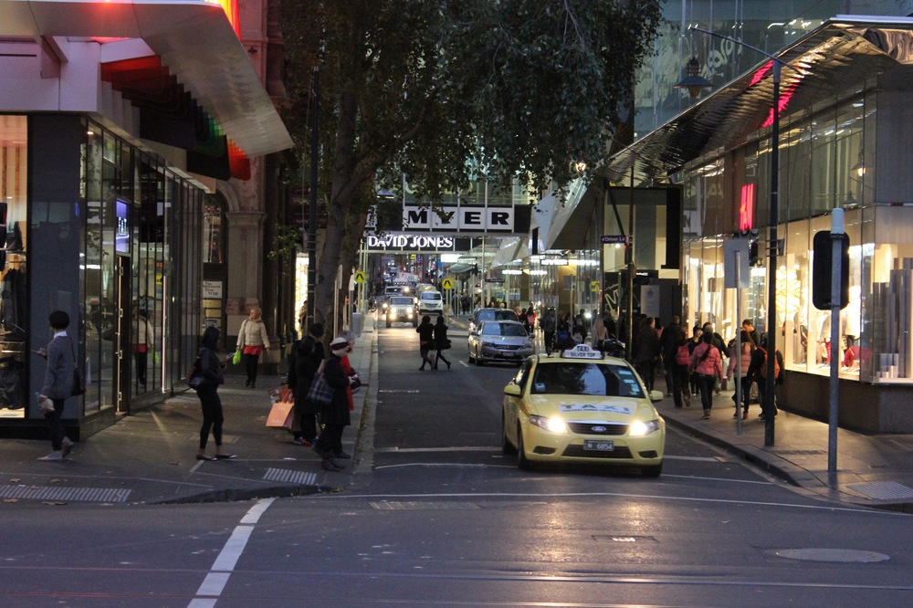 People jaywalking a street in Melbourne.