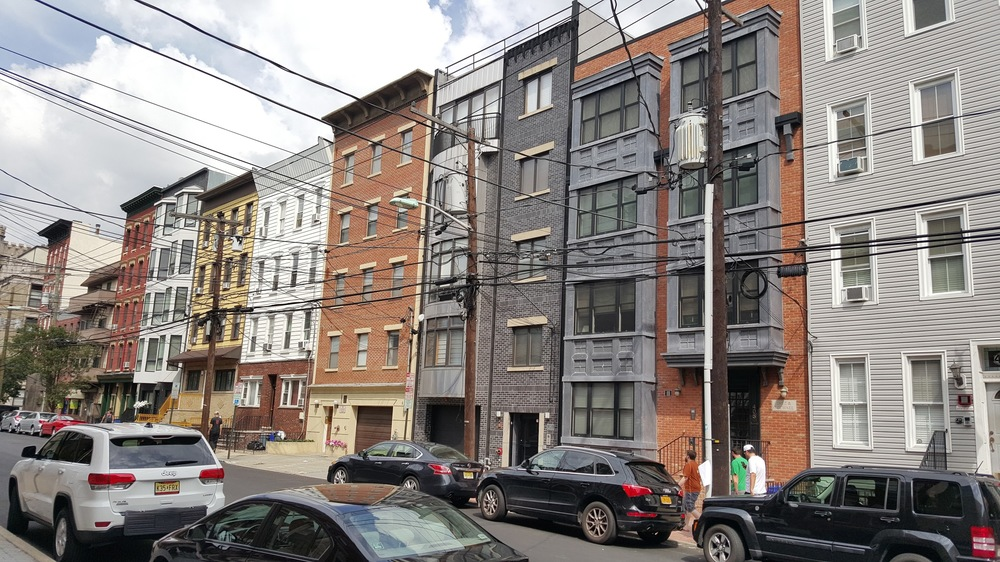 There is a mixture of older and newer buildings along this street in Hoboken. Here they are around 4 to 5 stories, and I have seen taller buildings in Manhattan while still being relatively fine grained, so I do not think that density is really an argument for coarse-grain development.