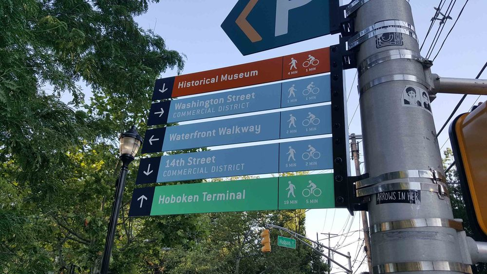 A wayfinding sign in Hoboken to nearby landmarks with distances for walking and cycling.