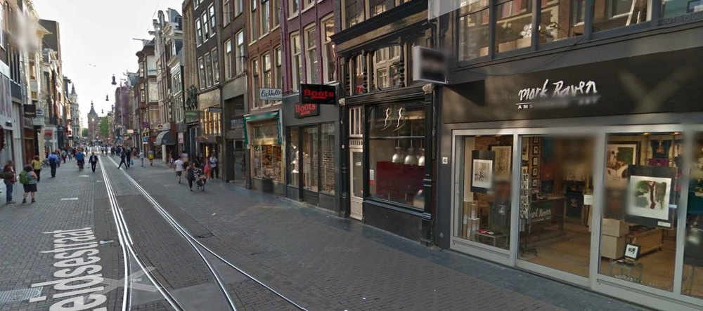 Shops in Amsterdam along a 35 foot wide street.  (Map.)