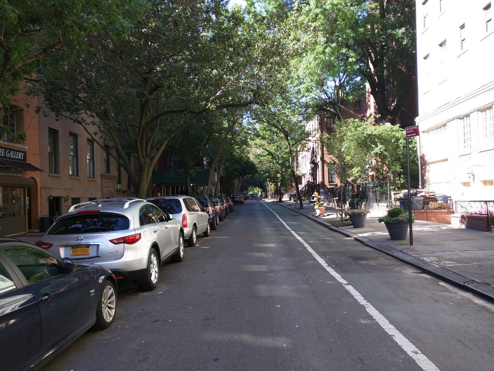 The (fading) green lane --demarcated with white line-- is a bike lane. Of particular importance to walkability are the street trees, as seen in both photos. Street trees provide shade on hot summer days, and a splash of natural color against what would otherwise be a hard urban environment. (Photo by Alexander Dukes)