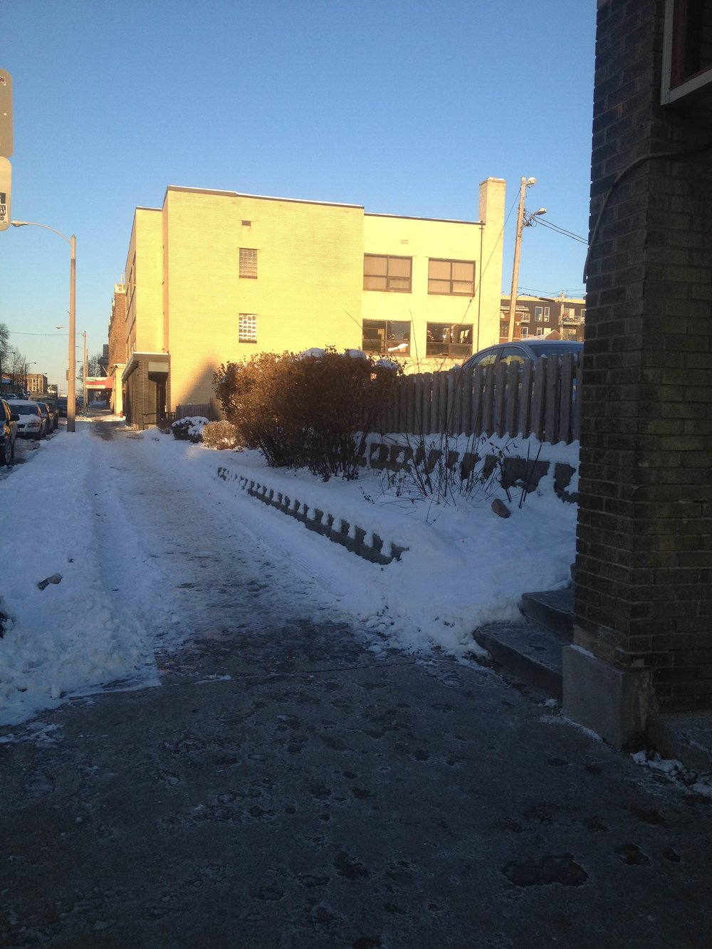 Photo taken a few blocks from my house in Milwaukee, where you can clearly see the shoveling line between the neighborhood pizza parlor (out of frame to the right) and the surface parking lot next door.
