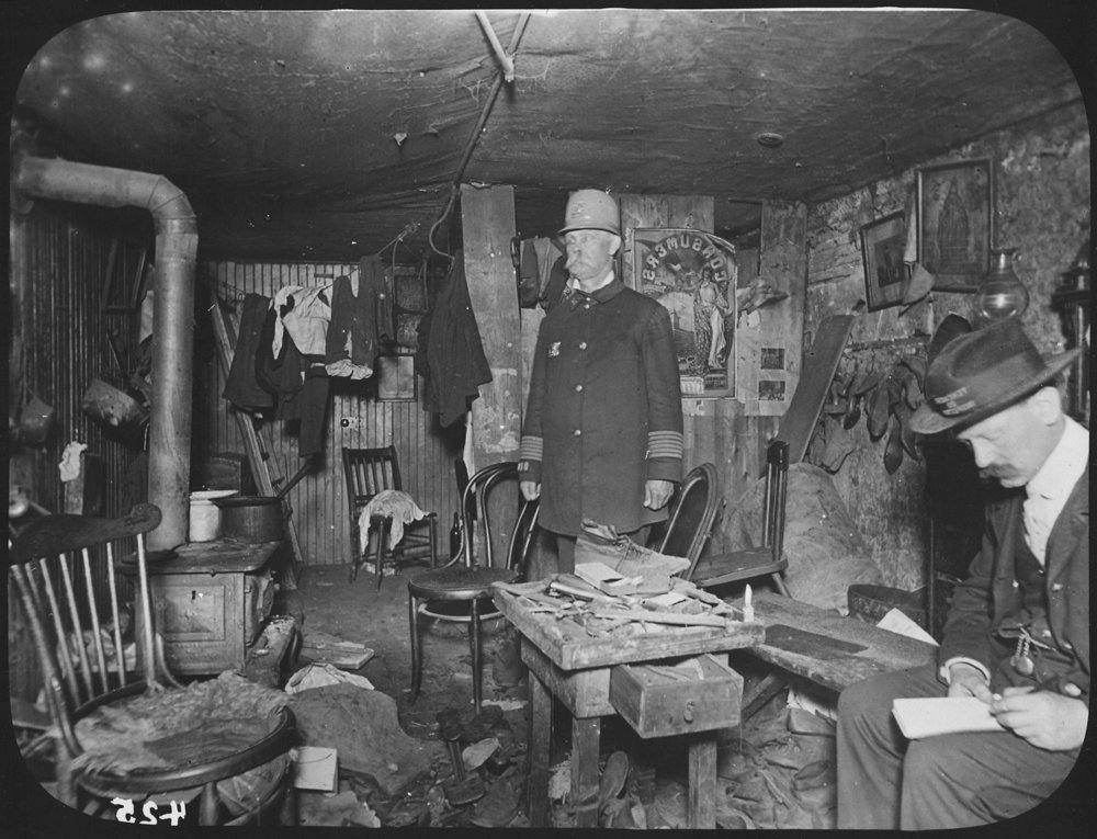 Two_officials_of_the_New_York_City_Tenement_House_Department_inspect_a_cluttered_basement_living_room,_ca._1900_-_NARA_-_535469.jpg