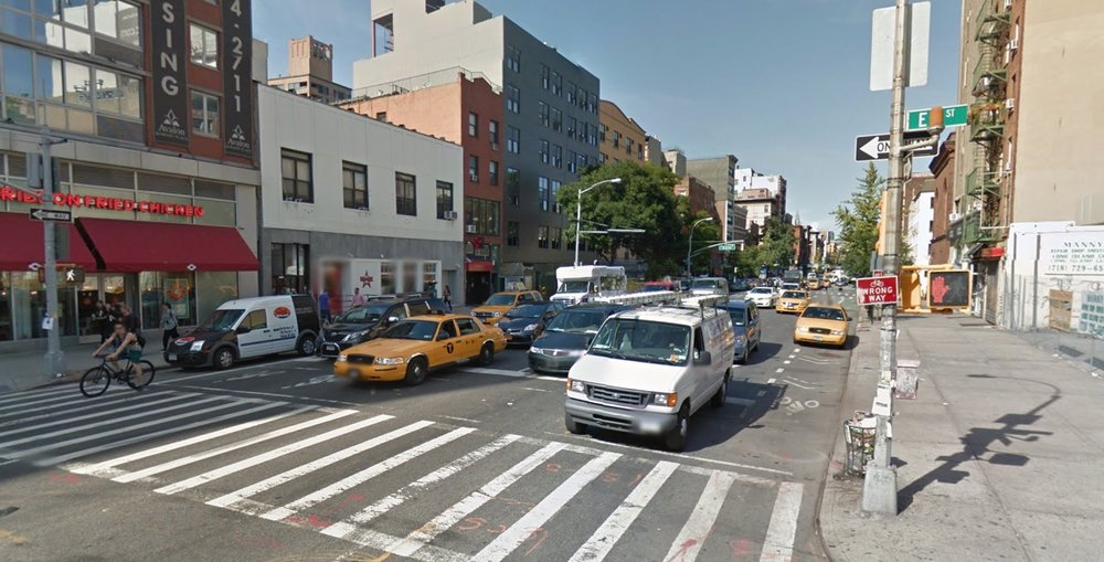 The street where Sam was struck. Note that the bike lane (currently occupied by a taxi) is merely striped here, not protected. (Image from Google Maps)