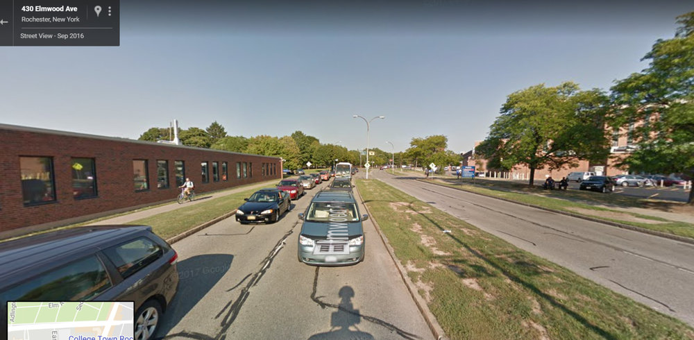 Google Street View of Elmwood between the University of Rochester campus and College Town.  Traffic congestion, higher speeds, no shoulders or bike lanes and the bare minimum pedestrian infrastructure make this a less-than-inviting on-foot experience for students.