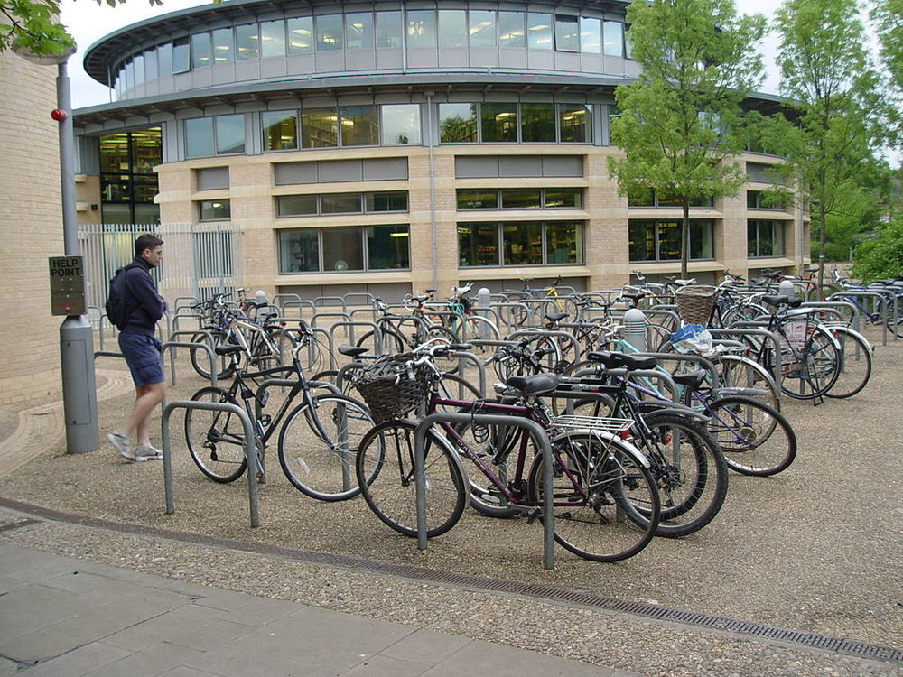 Bike parking near the entrance of a university building makes door to door transportation easy and keeps bikes safe under the watchful eye of passersby. (Source: Christian Mercat)