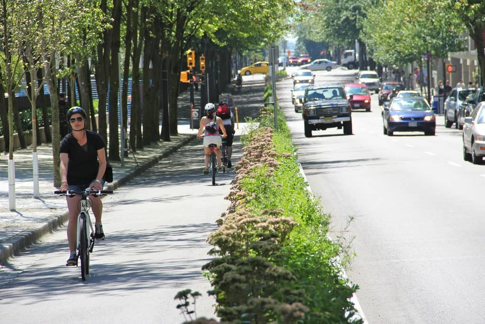 A protected bike lane helps everyone travel quickly and safely on a  road  where cars are driving fast (Source: Paul Krueger)