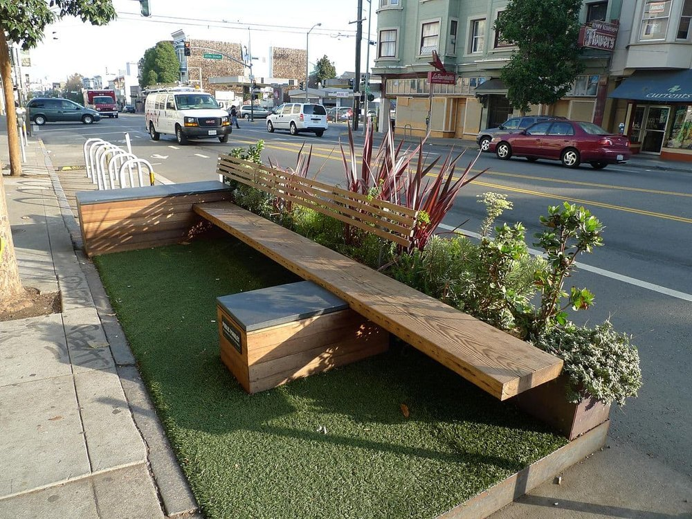 "A temporary ""parklet"" in the street helps slow cars and create seating in a quick and easy manner. (Source: Mark Hogan)"