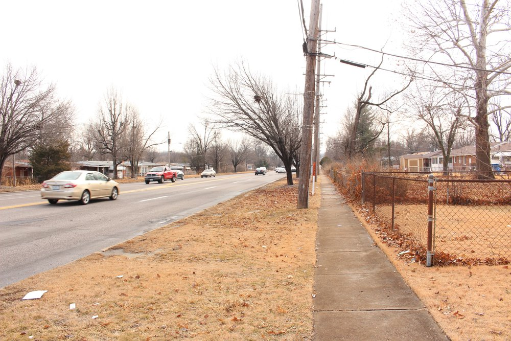 Narrow sidewalks next to speeding cars is a dangerous combination on West Florissant in Ferguson. The lack of safe crossings makes this street even more hostile to anyone outside a car. (Source: Aubrey Byron)