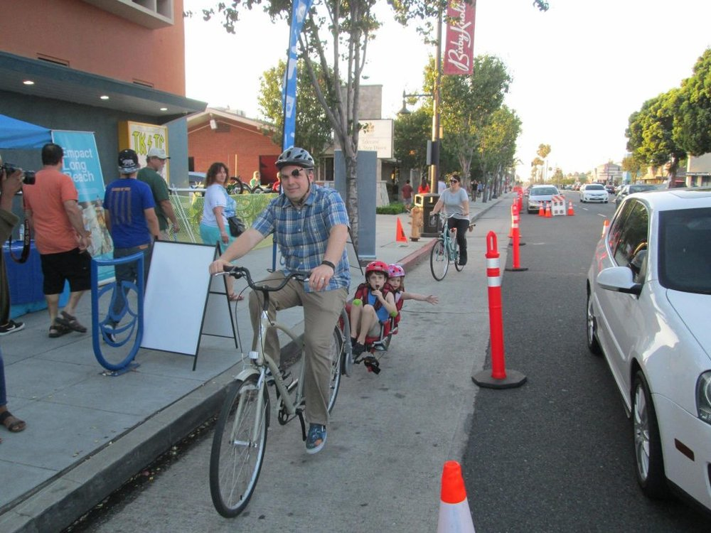 A temporary bike lane helps narrow a street and create safer transportation options (Source:  Bike Long Beach )