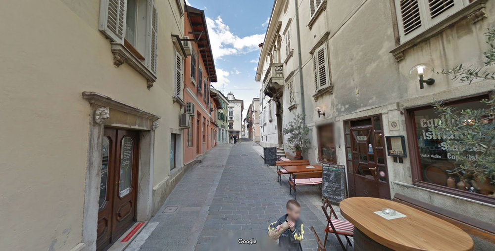 Koper, Slovenia. Not much different from a favela except they were able to afford fancier architecture, so we have a habit of glass casing places like this while also killing the systems that allowed these places to emerge. (Source:  Google Maps )
