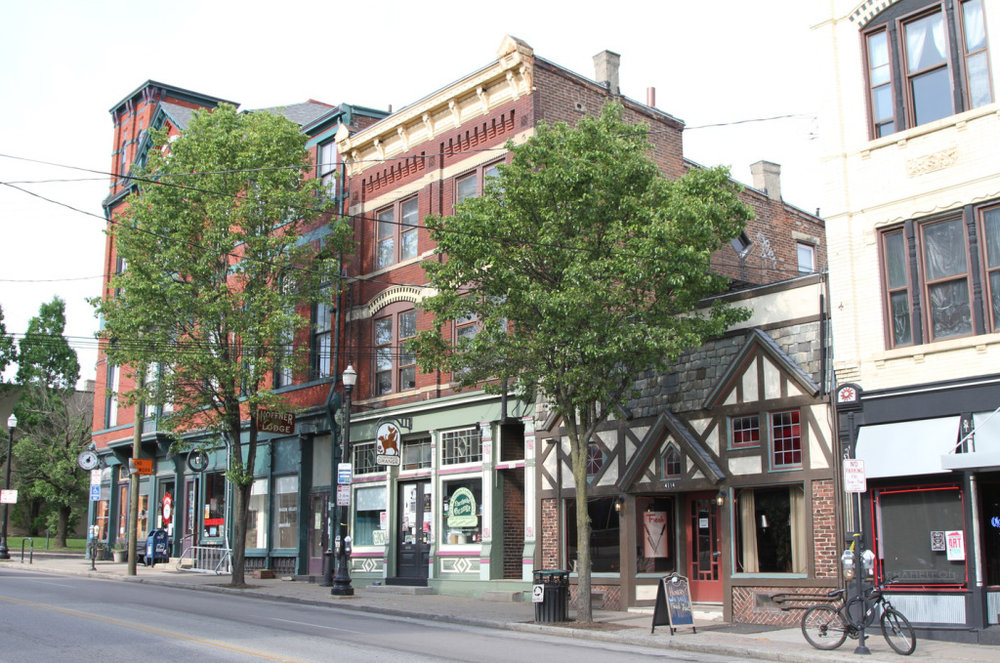 Small storefronts and apartments line a historic urban street. Let's get back to building more like this. (Source: Johnny Sanphillippo)