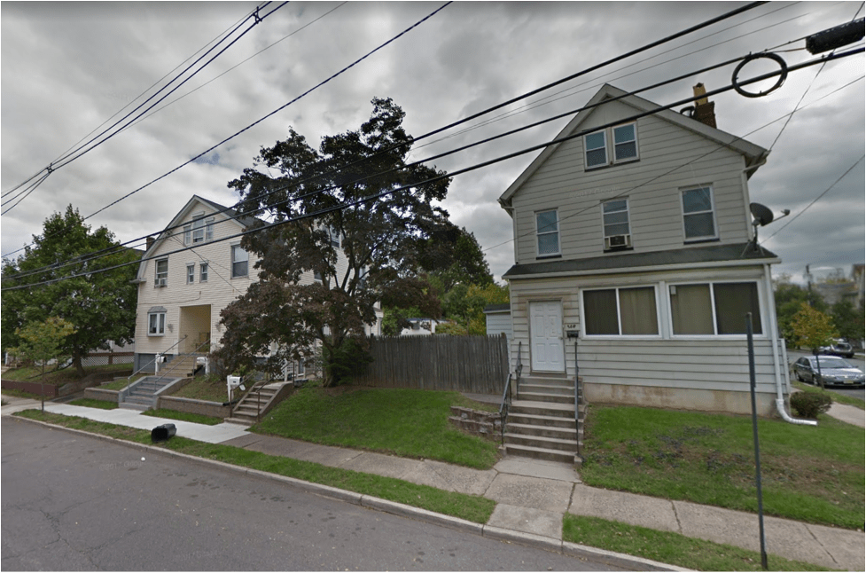A vacant lot in New Brunswick between these two houses has been absorbed by the property owners instead of being put to productive use. (Source: Google Earth)