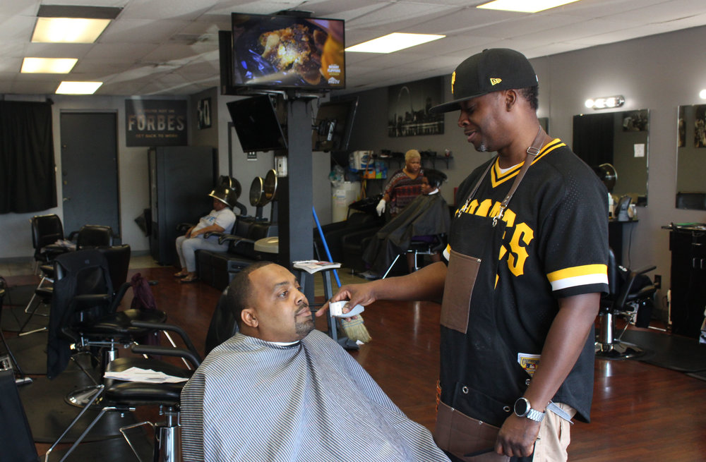 Carl Walker, owner of Klippers, as he trims Paul Berry III, a local candidate for St. Louis County Executive. (Photo by Aubrey Byron)
