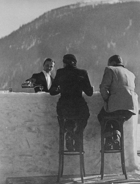 British couple sitting on high stools at ice bar outdoors at Grand Hotel St. Moritz . (Photo by Alfred Eisenstaedt)