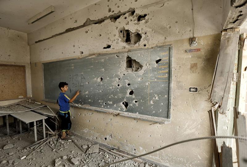 A Palestinian boy writes on a shrapnel riddled backboard at the heavily damaged Sobhi Abu Karsh school in Gaza City's al-Shejaea neighborhood on August 5, 2014. (Mohammed Abed)