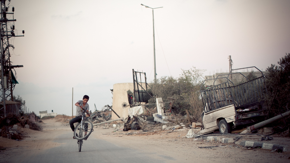 A young man rides his bicycle through Khuza'a in Khan Yunis. Sixty percent of homes were destroyed and two thirds of the residents were left homeless. (Tyson Sadler)