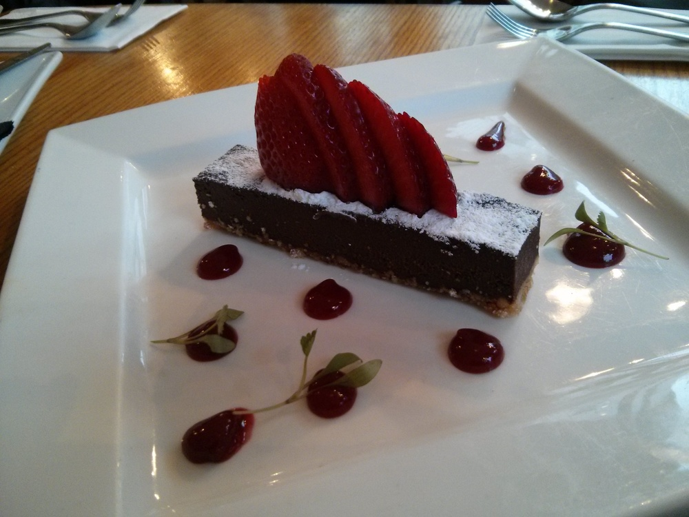 Chocolate truffle torte baked on a hazelnut biscuit base served with berry coulis