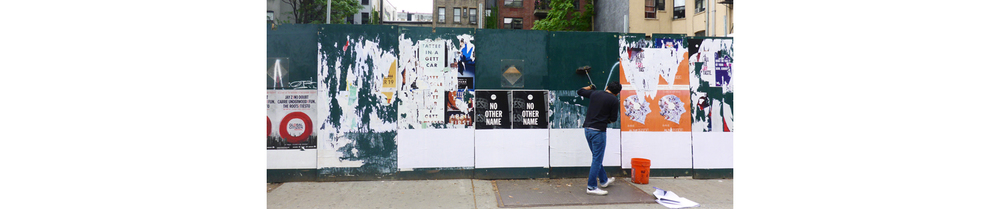 David, a paid contractor, illegally wheat pastes posters on a construction site on 14th street in Manhattan.